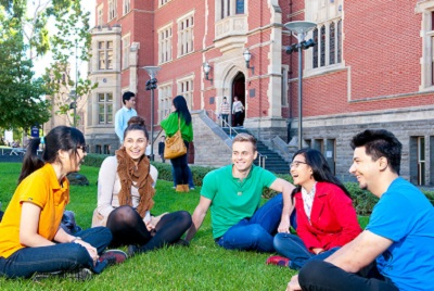 Students sit on the lawn in front of Brookman Hall